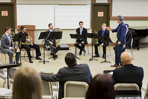 Stamps Brass Quintet receiving instruction in a class while an audience looks on