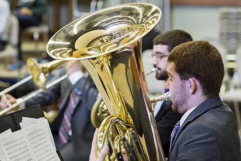 Tuba player in a gray suit is playing while looking at sheet music