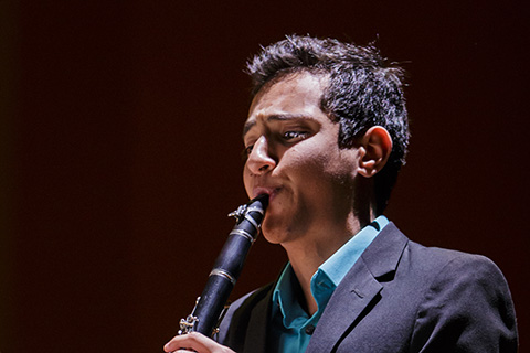 Man with dark hair in a dark suit plays the clarinet