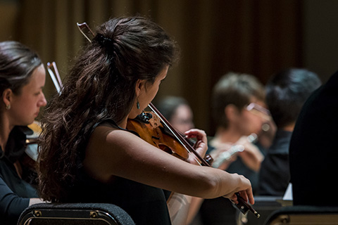 A violinist with dark hair is playing during a performance