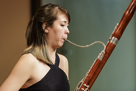 A classical musician plays the bassoon