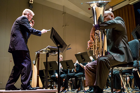 A tuba player performs with an orchestra as a director gestures with a baton