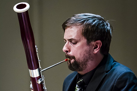 Musician in a dark suit plays the Bassoon
