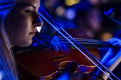 A woman under blue light plays the violin