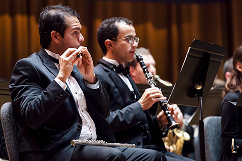 Classical musicians play wind instruments during a performance