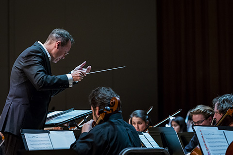 A conductor with a baton is guiding an orchestra during a performance