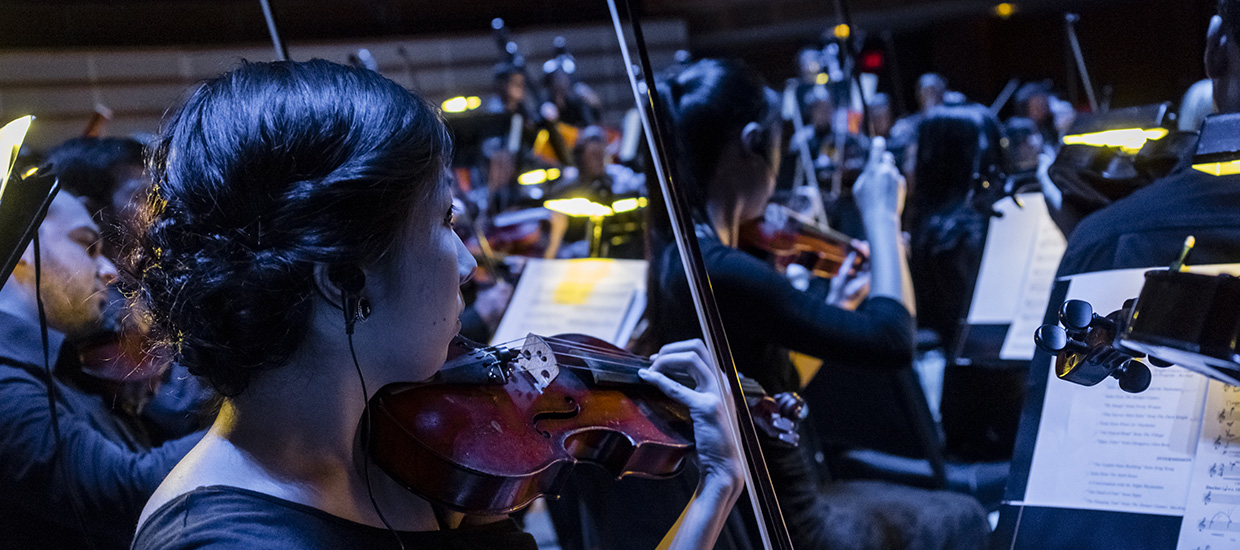 A woman with dark hair plays the violin along with the other musicians during a performance