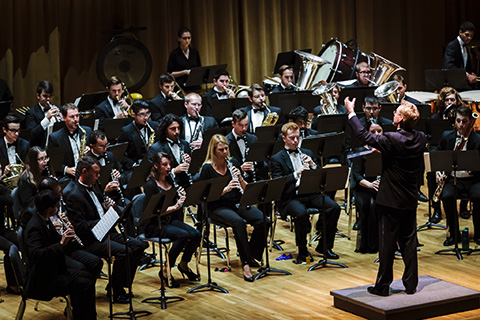 A conductor on a podium guides an orchestra during a live performance